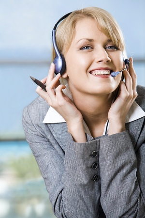 Portrait of beautiful smiling blond businesswoman in gray suit touching headset on her head in front of opened laptop photo
