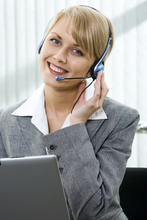 Portrait of beautiful smiling blond businesswoman in gray suit holding a pen in her hand and touching headset  photo