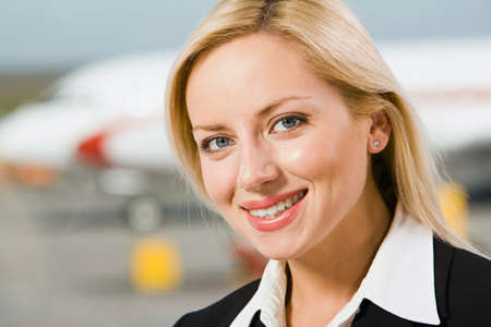 Portrait of beautiful woman with charming smile in an airport photo