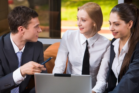 Smart businessman and two young women sitting on orange sofa at the table looking at the laptop  photo