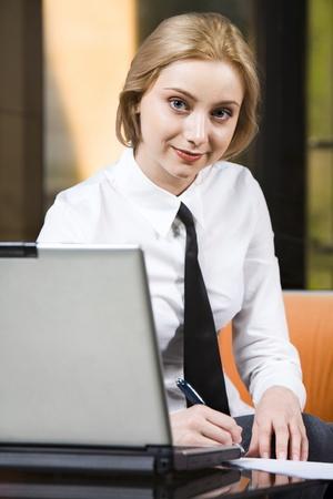 Beautiful writing businesswoman working on the laptop staring at camera photo