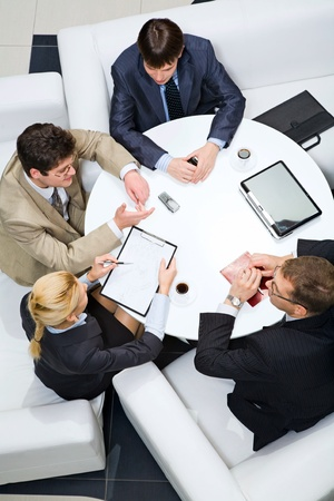 Group of people sitting at the table and discussing business questions photo