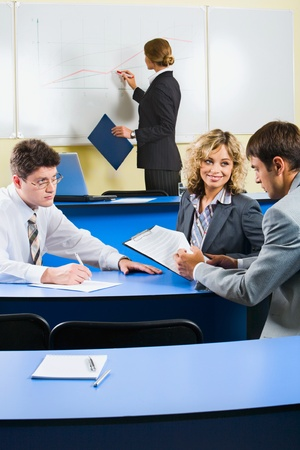 Group of people sitting at the blue table and discussing business questions in the class room Stock Photo - 8394573