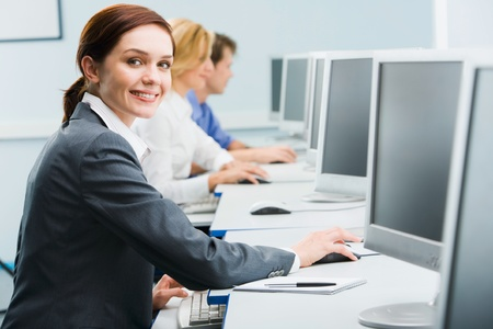 computer training: Portrait of busy woman sitting at the computer table and touching computer mouse on the background of businesspeople