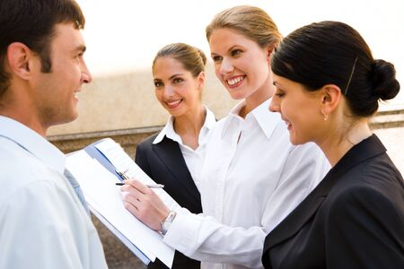 Team of young smiling professionals are discussing  new business ideas background of a building photo
