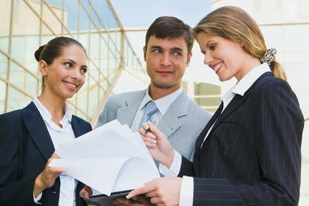 Successful people discussing a plan on the background of building  photo