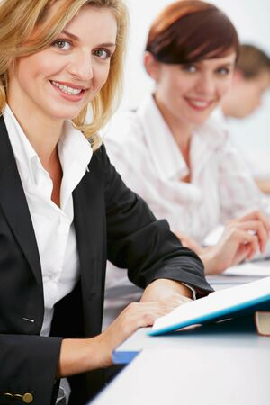 Confident businesswomen is sitting at the table with books on it Stock Photo - 8394831