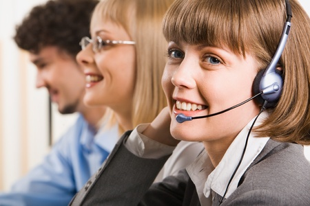A friendly smiling customer support operator on a background of two business people Stock Photo - 8395091