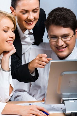 Business woman is explaining the correct way of analysis to his colleagues in  the office pointing at he monitor Stock Photo - 8395052