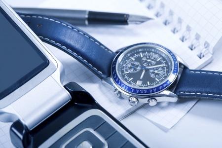 Creative photo: telephone, wrist-watch, notepad and fountain-pen photo