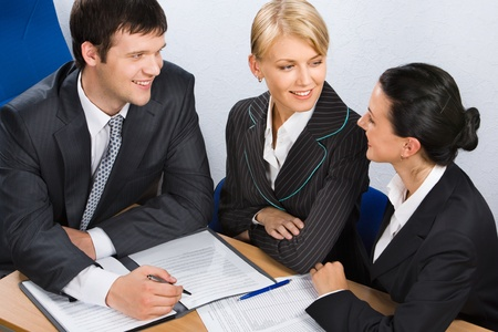 team leadership: Three young business people discussing interesting idea in the office