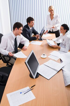 Team of young smiling professionals discuss a plan in the conference room Stock Photo - 8394835