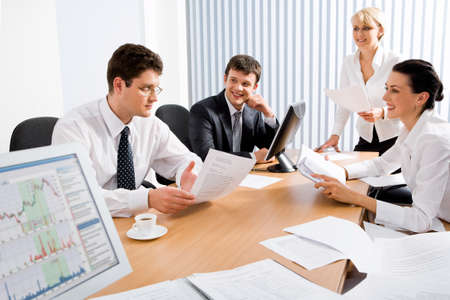Portrait of four professionals sitting at the table and discussing a business idea in the office photo