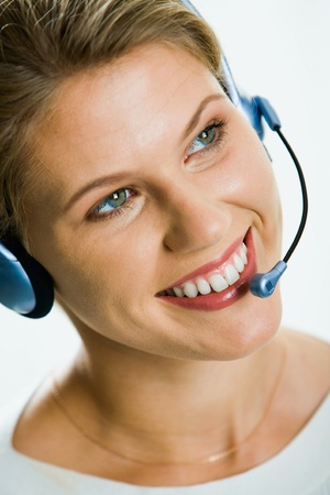 Close-up of young attractive smiling businesswoman speaking on the headset Stock Photo - 8395461
