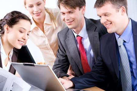 Portrait of four confident colleagues discussing a business plan  photo
