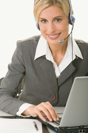 Portrait of friendly smiling customer support operator sitting at the table in a working environment photo