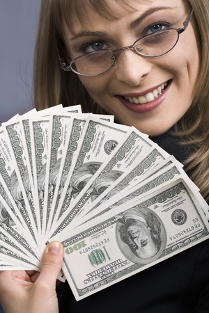 Smiling girl fanning herself with of bank notes   photo