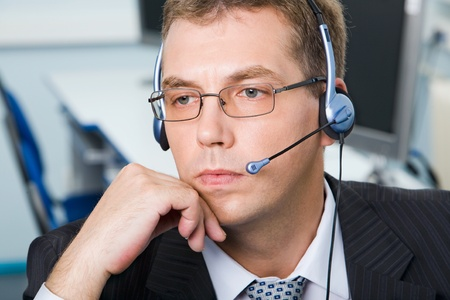 Serious businessman with glasses and headset in the office photo