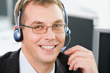 Portrait of  smiling negotiator with glasses and headset  photo