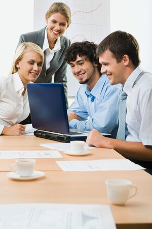 Team of successful business people sitting at the table with laptop, papers and cup on it discussing important questions Stock Photo - 8395163