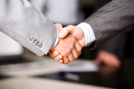 Successful handshake of business men in a working environment photo