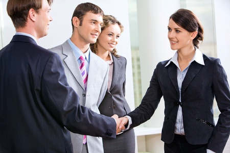 businesswear: Businessman and businesswoman shaking hands in the hall