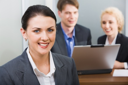Young beautiful smiling woman in a working environment on a background of her business team photo