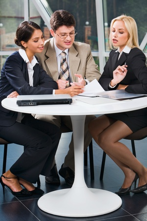 Group of three young business people gathered together at a table discussing an interesting idea in the cafe photo