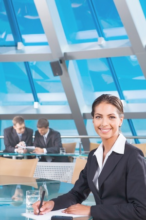 Portrait of confident woman sitting at the table and looking at camera in the conference room photo