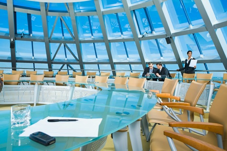Customary conference room: glassy table, chair, large window photo