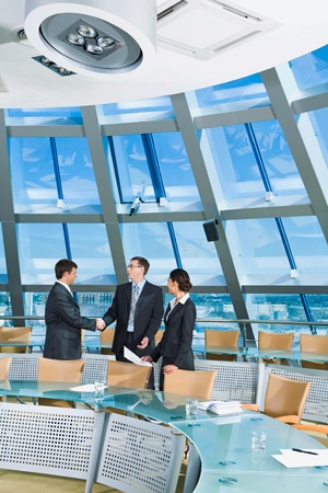 boardroom meeting: Businessmen shaking hands in the conference room Stock Photo