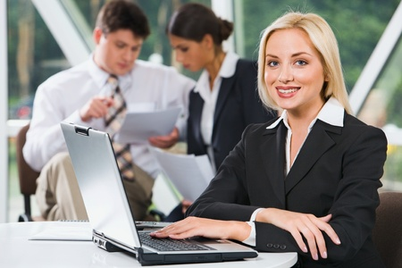 Young successful smiling woman sitting at the table with laptop and note on it photo