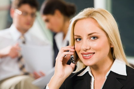 Businesswoman is talking to her cell-phone discussing important questions photo