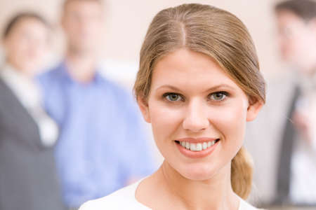 Beautiful face of smiling woman on the background of businesspeople  photo