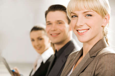 executive assistants: Line of young smiling specialists looking at camera