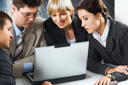 Group of four young specialists gathered together around the laptop discussing important project in the office photo
