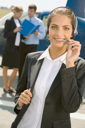 Beautiful pilot with headset smiling on a background of two business people and helicopter photo