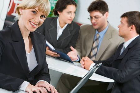 Confident young woman on the background of three business people Stock Photo - 8395708