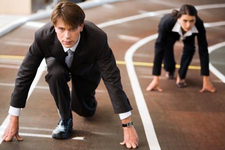 Zaken man en zaken vrouw opgesteld klaar voor race in het bedrijfsleven