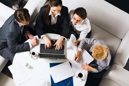 networking people: Retrato de cuatro empresarios sentado a la mesa delante del ordenador port�til abierto y serio mirando en la pantalla Foto de archivo