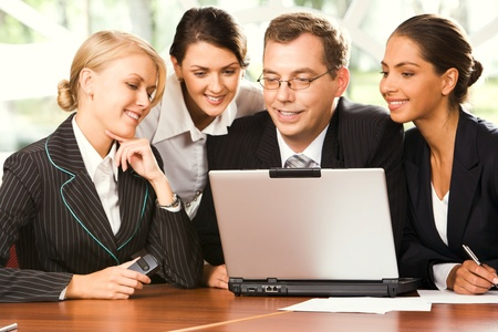 Portrait of four businesspeople sitting at the table in front of opened laptop and seusly gazing at the screen Stock Photo - 8398918