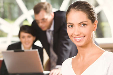 Portrait of smiling brunette Caucasian woman and two talking businesspeople on the background working on the laptop Stock Photo - 8398875