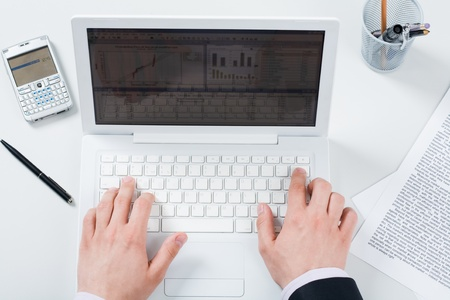 Above view of male hands pushing buttons of laptop with smartphone and papers near by photo