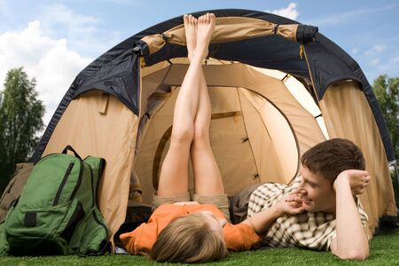 Pretty girl touching boyfriend while lying on grass near tent during summer vacations photo