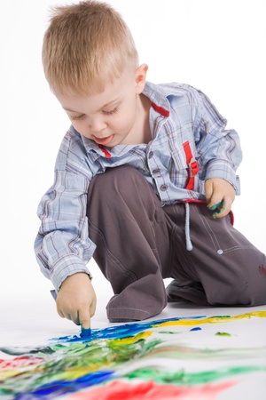 keen: Photo of cute preschooler painting something with colorful gouache