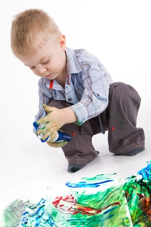 keen: Photo of cute lad holding container with colorful gouache while painting