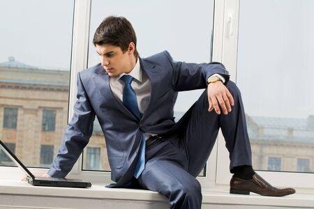 hombre sentado: Foto de hombre de negocios inteligente, sentado en el umbral de la ventana con port�til cerca por y mirando de monitor