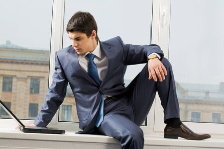 windowsill: Photo of smart businessman sitting on window-sill with laptop near by and looking at monitor