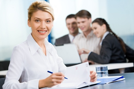 Contemporary woman is sitting at the table on the background of business team  photo
