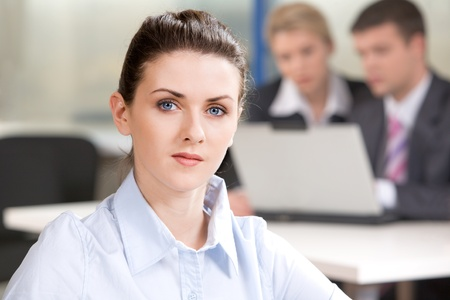 spokesperson: Portrait of serious business woman on the background of her colleagues Stock Photo